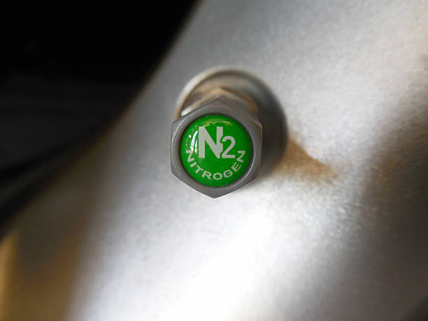Plastic TPMS Safe Nitrogen Valve Cap on Aluminum Stem/Alloy Wheel A gray plastic TPMS-safe nitrogen valve cap on an alluminum stem/alloy wheel nitrogen stock pictures, royalty-free photos & images