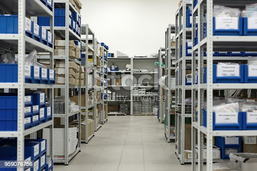 A small warehouse of spare parts and components of industrial electronics. Plastic trays and cardboard boxes in metal racks.