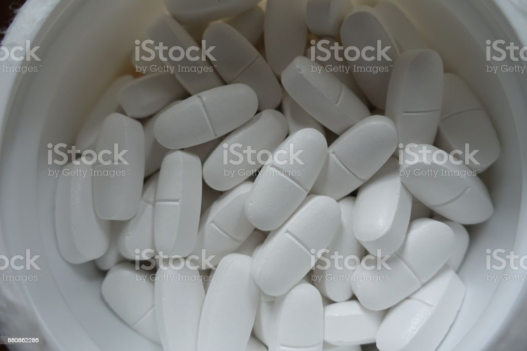 Plastic tub filled with white caplets from above stock photo