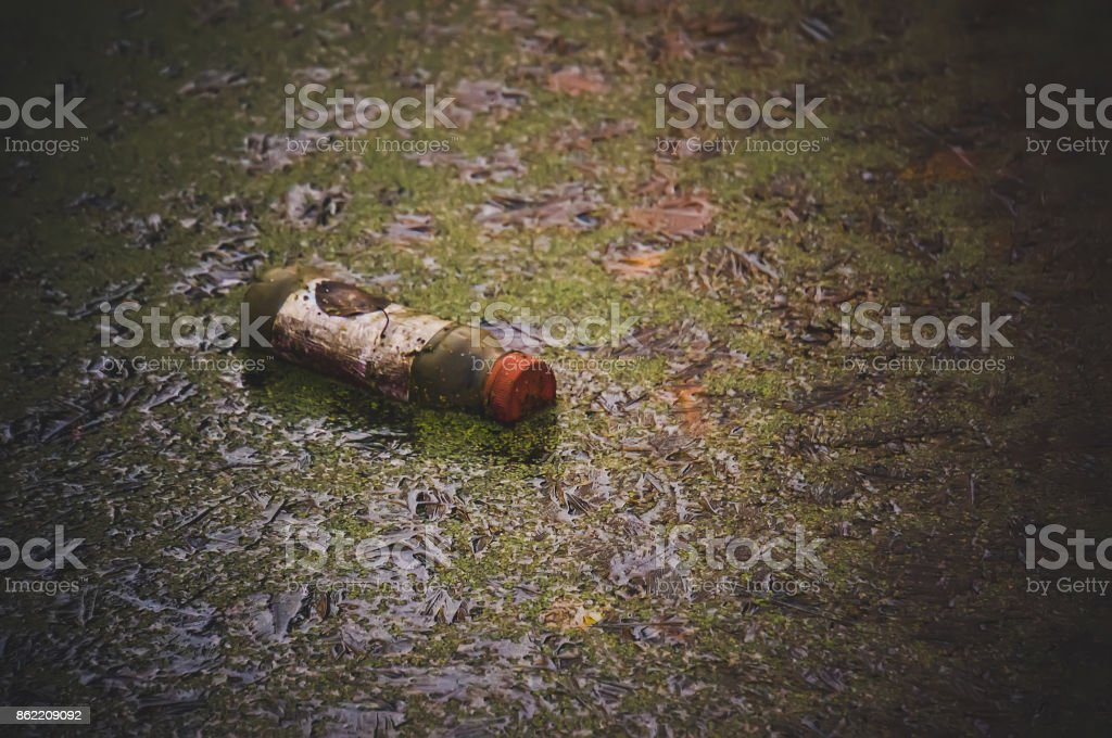 Plastic waste in the dirty water and green grass stock photo