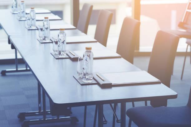 Plastik-Wasserflaschen, Trinkgläser mit Bleistift und Weißpapieren auf dem Tisch für Seminar- oder Geschäftstreffen im Konferenzraum des Hotels vorbereitet – Foto