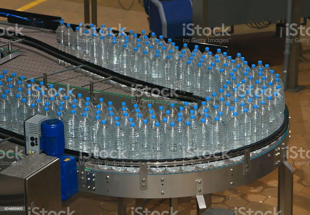 Plastic water bottles on conveyor stock photo