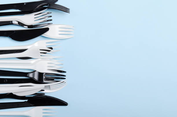 Plastic white and black disposable forks and knives on a blue background. Plastic dishes. Copy space, top view, flat lay. stock photo