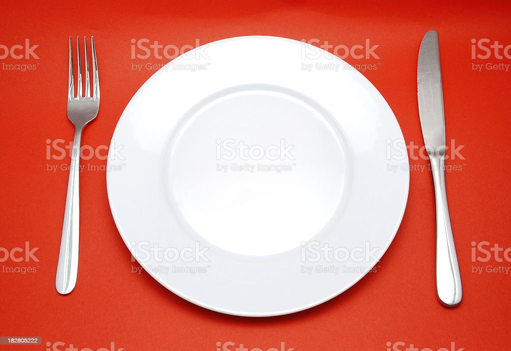 Plate, Fork and Knife isolated on red royalty-free stock photo