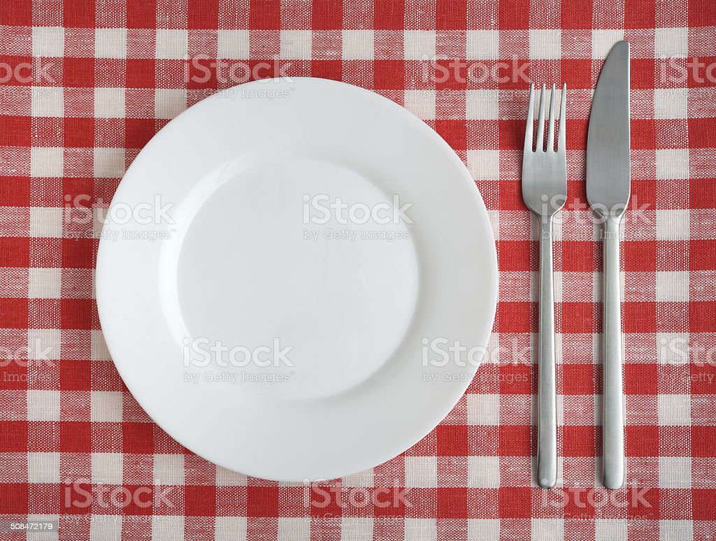 Plate, fork, knife on a red checkered tablecloth. stock photo
