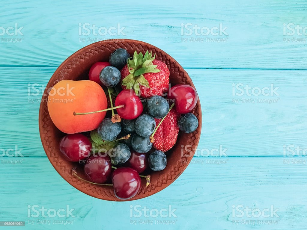 plate, fruit berries, cherry, strawberry, blueberry on a blue wooden background zbiór zdjęć royalty-free
