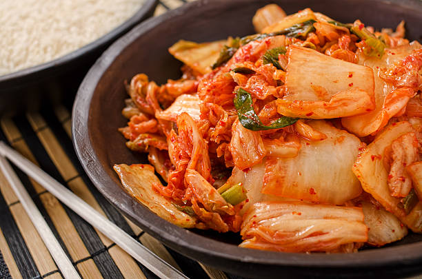 Plate full of kimchi and chopsticks on side stock photo