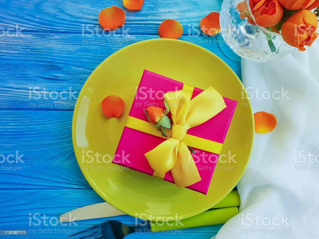 plate, gift box, flower rose on a blue wooden background