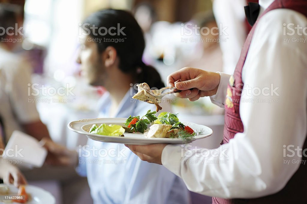 Plate in waiter's hands stock photo
