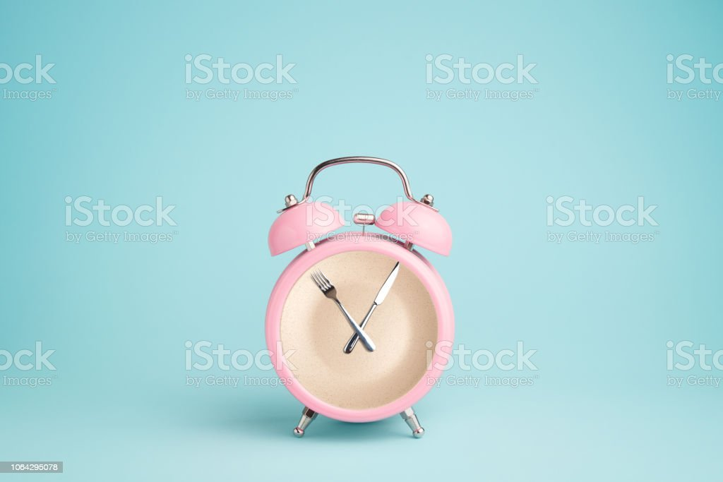 Plate inside the pink alarm clock. Concept of intermittent fasting, lunchtime, diet and weight loss stock photo