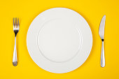Table setting with white plate, modern cutlery (fork and knife) on yellow table, top view, copy space.