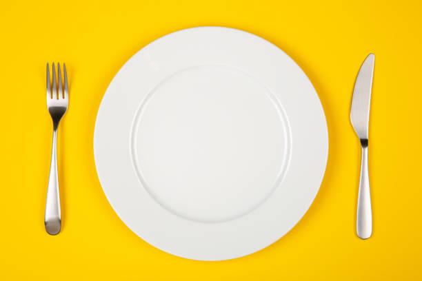 teller, messer und gabel auf gelbem hintergrund isoliert - tafelbesteck stock-fotos und bilder