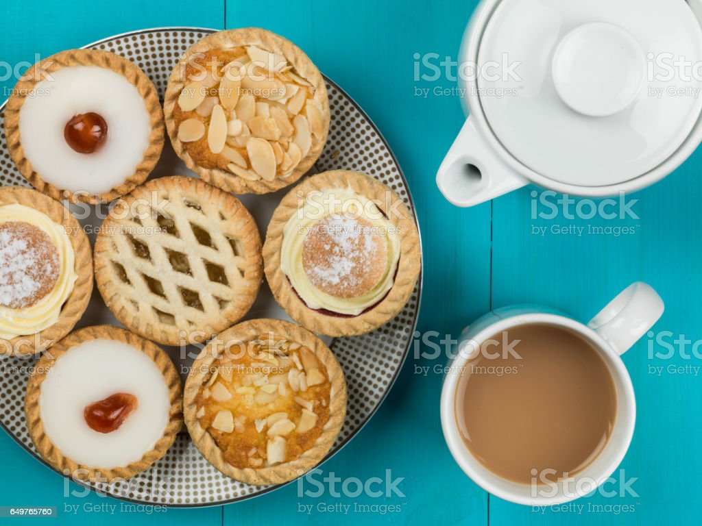 Plate of Assorted Individual Cakes or Tarts With a Pot of Tea stock photo