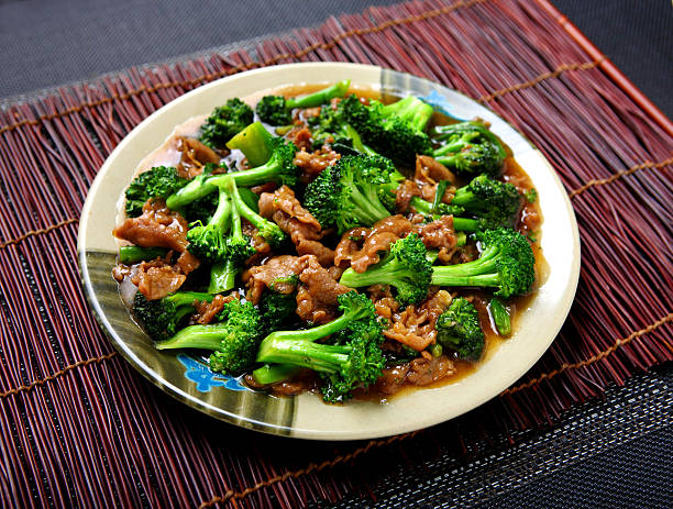 A plate of beef broccoli dish on top of table ready to eat stock photo
