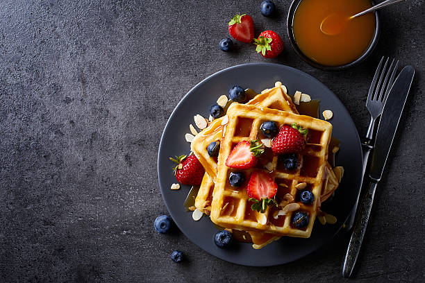 Plate of belgian waffles Plate of belgian waffles with caramel sauce and strawberries on dark gray background. From top view waffle stock pictures, royalty-free photos & images