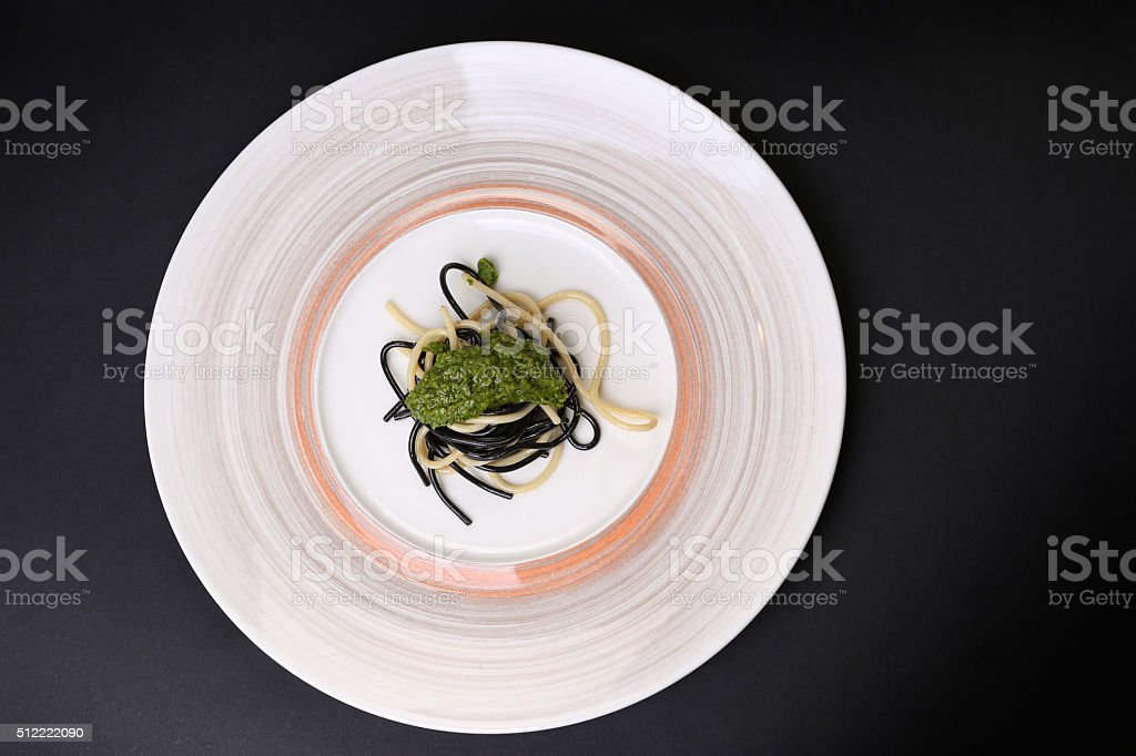Plate of black and white spaghetti with green souse stock photo