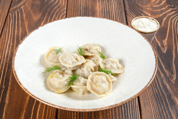 Plate of boiled dumplings with sour cream sauce on wooden table