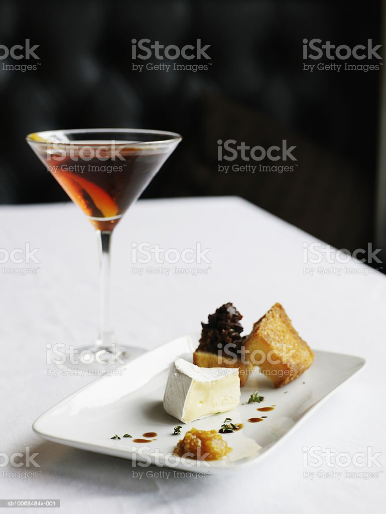 Plate of camembert cheese, quince paste, and bacon compote with cocktail foto royalty-free
