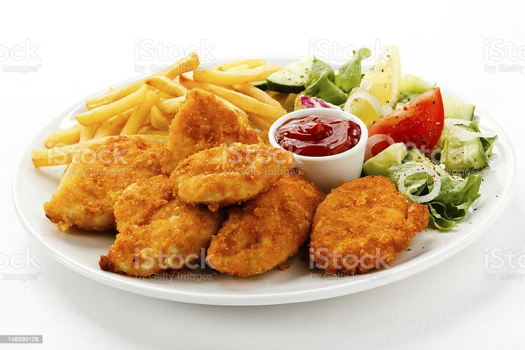 A plate of chicken nuggets, French fries and salad royalty-free stock photo