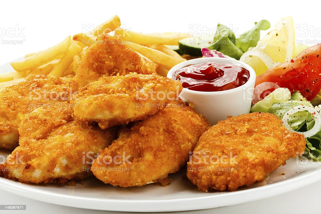 A plate of chicken nuggets with fries, a salad and ketchup stock photo