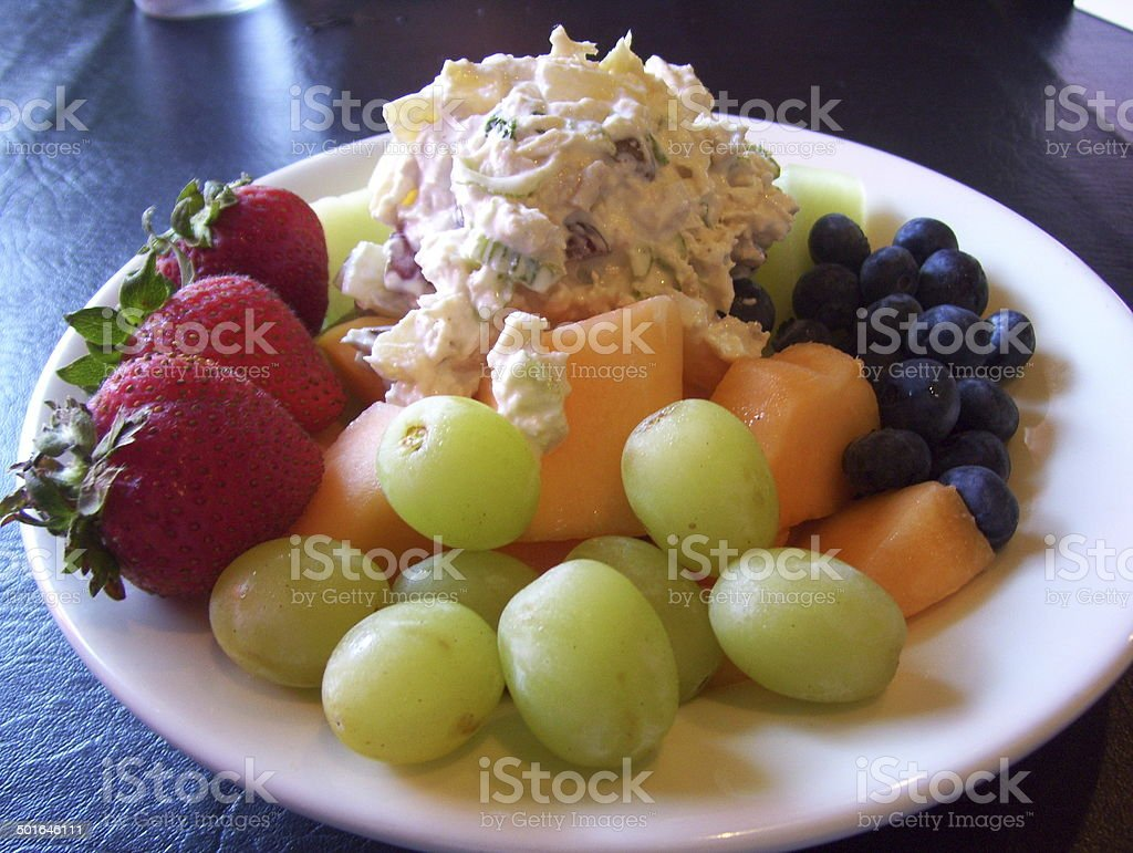 Plate of Chicken Salad with Colorful Fruit and Melons stock photo
