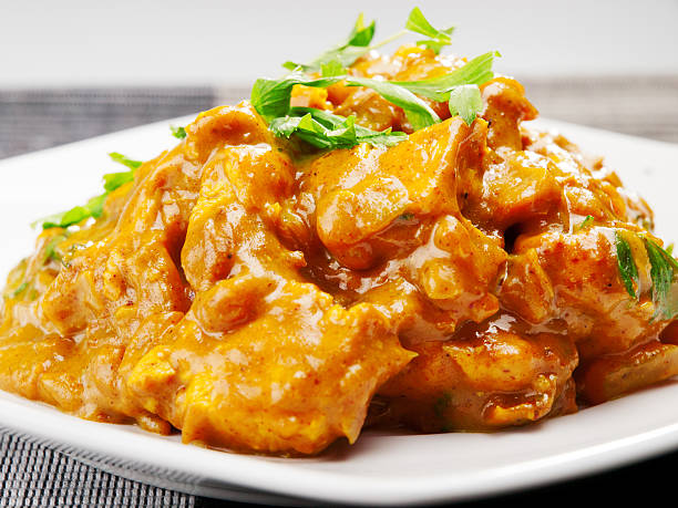 Plate of chicken tikka masala with garnish Chicken tikka masala - indian meal curry powder stock pictures, royalty-free photos & images