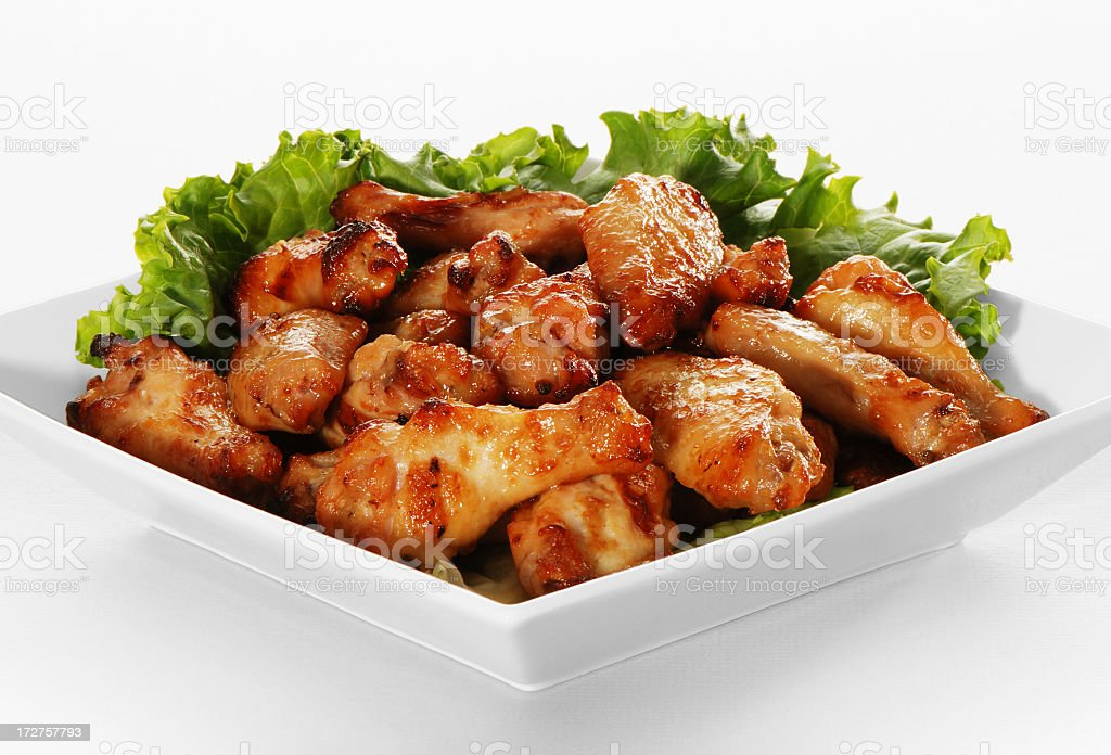 Plate of chicken wings with leaf garnish stock photo