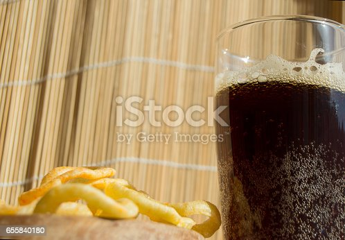 istock Plate of chips, a glass of dark beer with foam, bubbles on wooden background 655840180