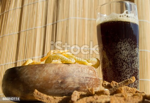 istock Plate of chips, glass of dark beer with foam, bubbles and crackers on wooden background 655840114