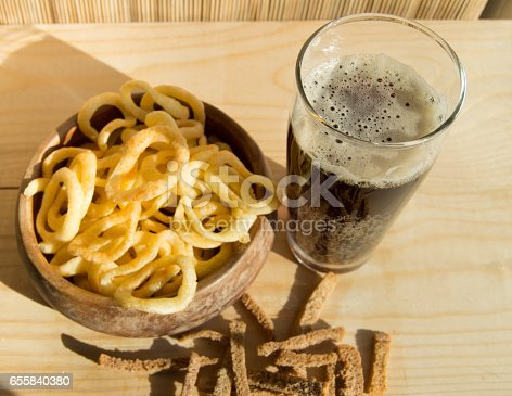 istock Plate of chips, glass of dark beer with foam, bubbles and crackers on wooden background Top view 655840380