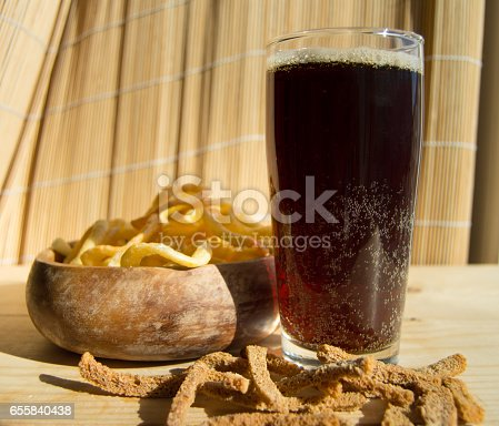 istock Plate of chips, glass of dark beer with foam, bubbles and crackers on wooden background 655840438