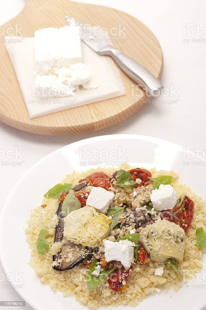 Plate of couscous with antipasto vegetables, and cheese cutting board. stock photo