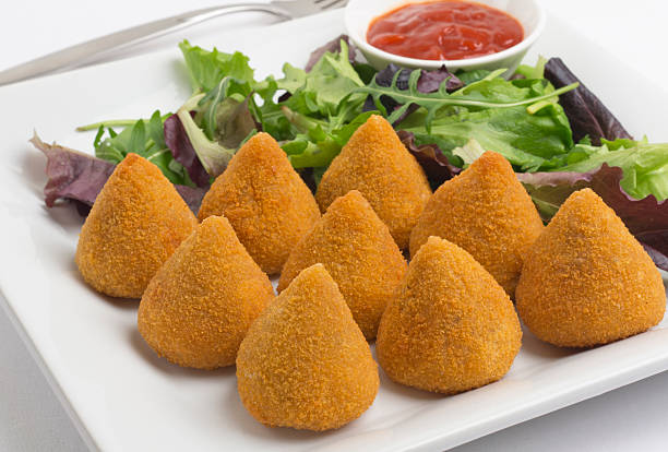 plate of coxinha de galinha with salad greens on white plate - coxinha stock photos and pictures