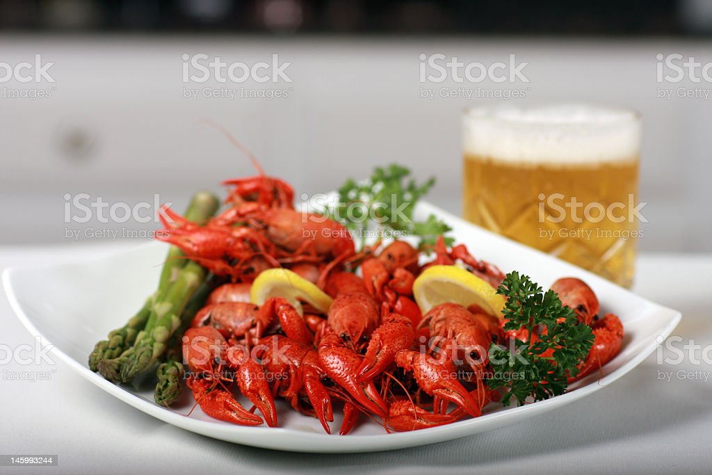 A plate of crawfish, asparagus, parsley and lemon with beer stock photo