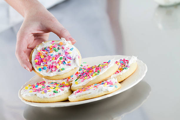 Plate of Decorated Sugar Cookies A hand reaching for a decorated sugar cookie on a plate. sugar cookie stock pictures, royalty-free photos & images