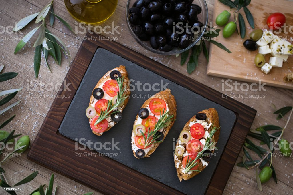 plate of delicious bruschetta on wooden table with fresh vegetables zbiór zdjęć royalty-free