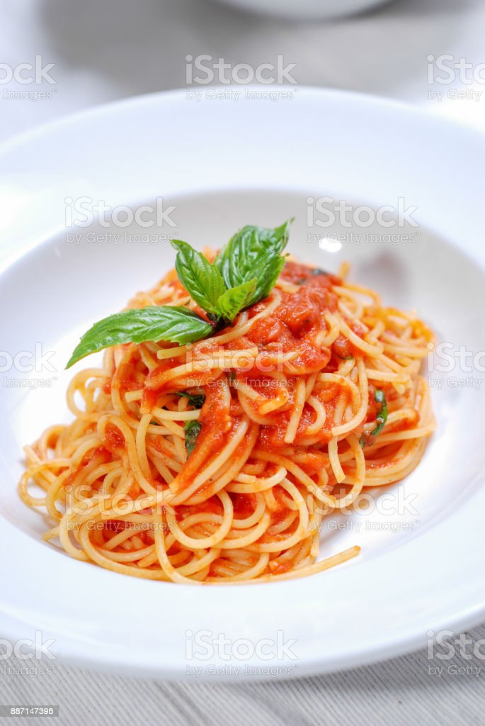 plate of delicious spaghetti with sauce and fresh basil stock photo