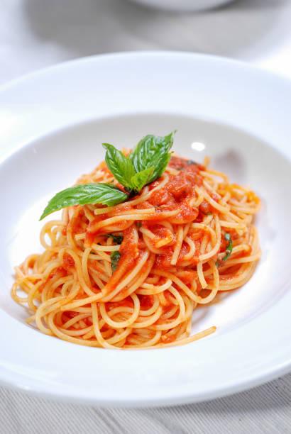 teller mit leckeren spaghetti mit soße und frischem basilikum - spaghetti tomatensauce stock-fotos und bilder