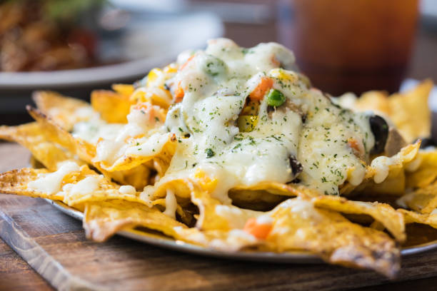 A plate of delicious tortilla nachos with melted cheese sauce and dressing. Food background. stock photo