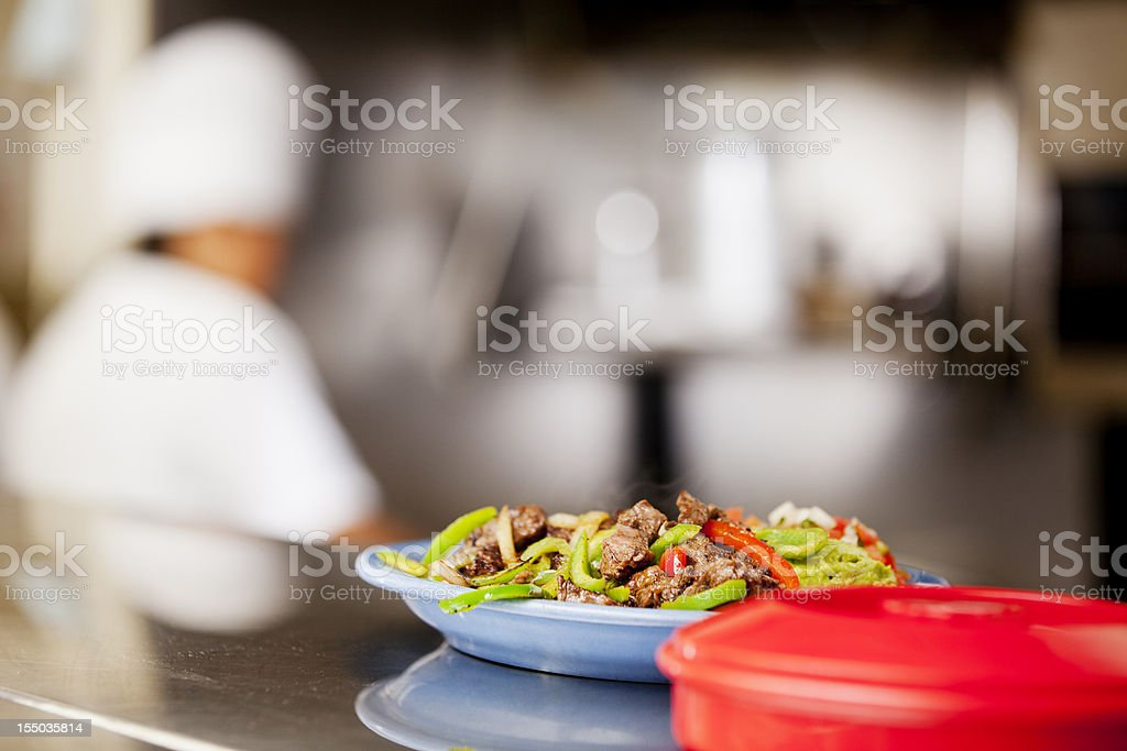 Plate of fajitas ready for serving with chef in background stock photo