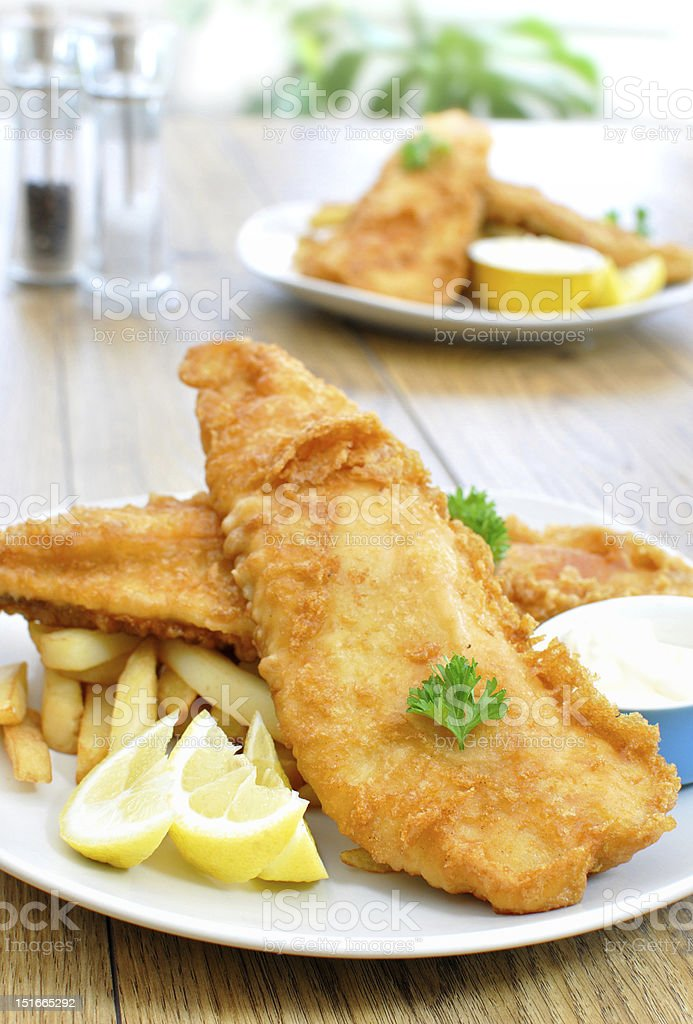 Plate of fish and chips on a wooden table stock photo