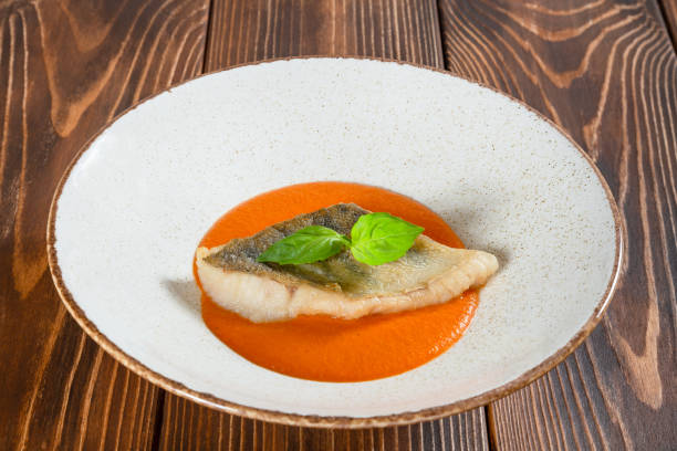 Plate of fish fillet with pumpkin sauce on a wooden table