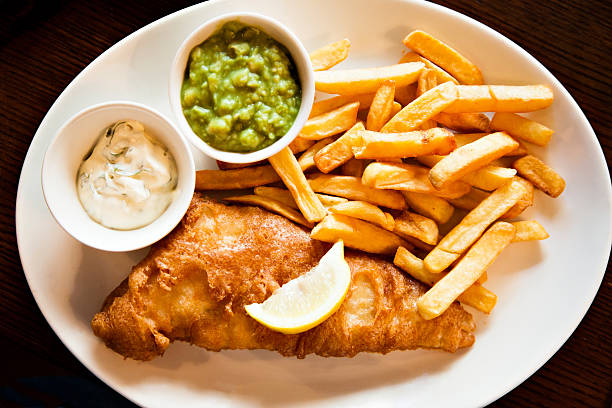 Plate of Fisn and Chips with tartar sauce mushy peas stock photo