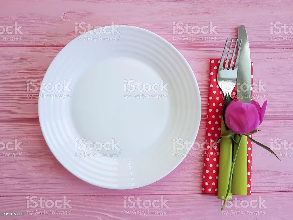 plate of fork knife flower peony on pink wooden background stock photo