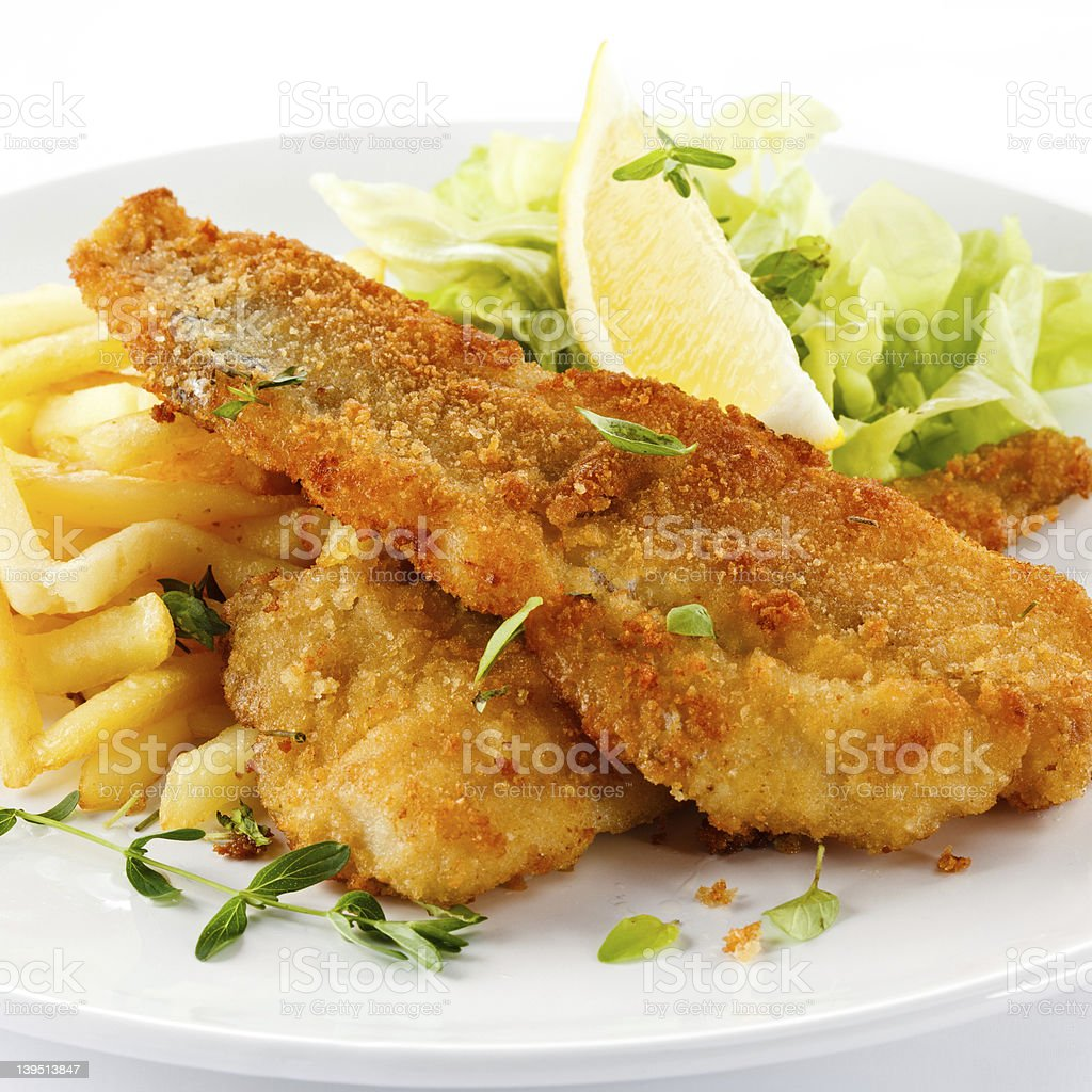 A plate of fried cod, with french fries and a salad stock photo