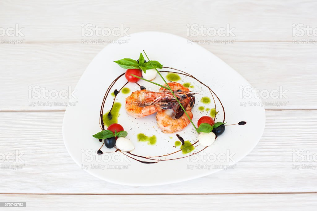 Plate of fried prawns on white wooden background stock photo