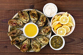 High angle view of a plate full of grilled artichokes on a rustic restaurant table.