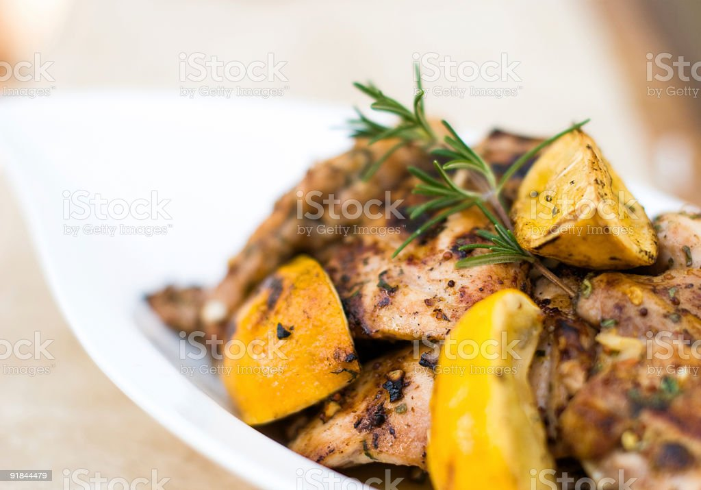 Plate of grilled chicken garnished with greens and lemons royalty-free stock photo