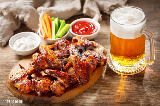 grilled chicken wings and mug of beer on a wooden board