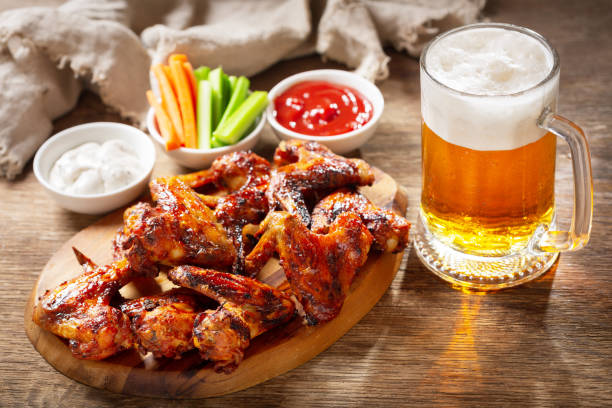 plate of grilled chicken wings and mug of beer stock photo